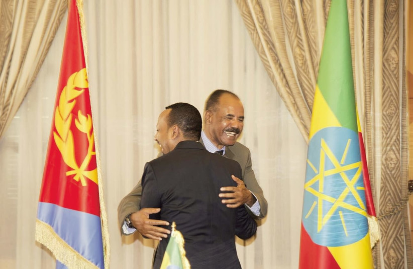 ETHIOPIA'S PRIME Minister Abiy Ahmed and Eritrean President Isaias Afwerk embrace at the declaration signing in Asmara, Eritrea on July 9. (photo credit: REUTERS)