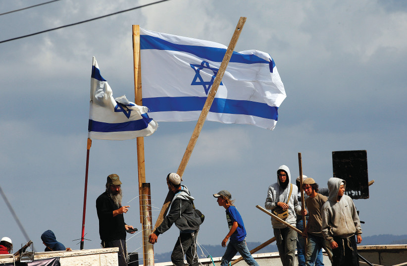 PROTESTERS CARRY wooden sticks as they stand on a roof during the evacuation of families from the illegal outpost of Netiv Ha'avot last month.  (photo credit: RONEN ZVULUN/REUTERS)