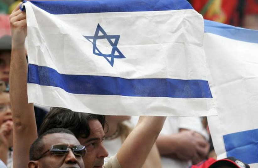A man holds up an Israeli flag at the start of a soccer match [Illustrative] (photo credit: REUTERS)