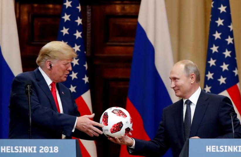 U.S. President Donald Trump receives a football from Russian President Vladimir Putin as they hold a joint news conference after their meeting in Helsinki, Finland July 16, 2018 (photo credit: GRIGORY DUKOR / REUTERS)