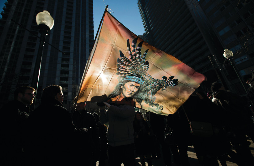 First nations protesters are silhouetted behind a flag as they take part in a demonstration in Toronto in 2013 (photo credit: REUTERS)