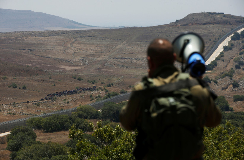An Israeli soldier speaks over a megaphone to people which stand next to the border fence between Israel and Syria from its Syrian side as it is seen from the Golan Heights near the Israeli Syrian border July 17, 2018. (photo credit: RONEN ZVULUN / REUTERS)