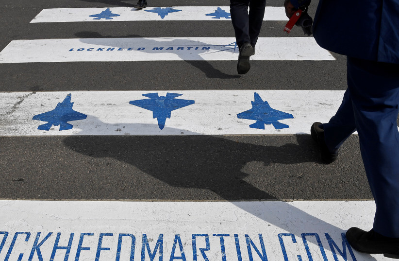Trade visitors are seen walking over a road crossing covered with Lockheed Martin branding at Farnborough International Airshow in Farnborough, Britain, July 17, 2018. (photo credit: TOBY MELVILLE/REUTERS)