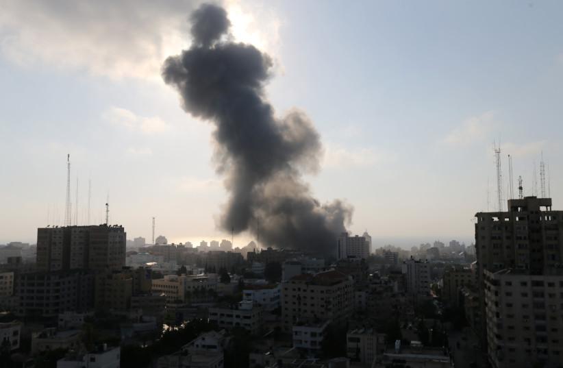 Smoke rises following an Israeli strike on a building in Gaza City July 14, 2018 (photo credit: REUTERS/IBRAHEEM ABU MUSTAFA)