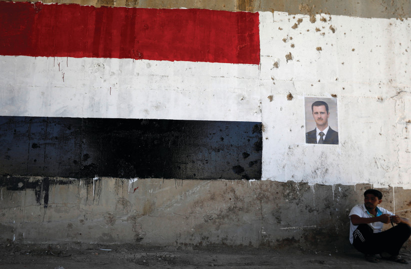 ON THE march. A poster of Syrian dictator Bashar Assad who is allied with Russia and Iran.  (photo credit: REUTERS)