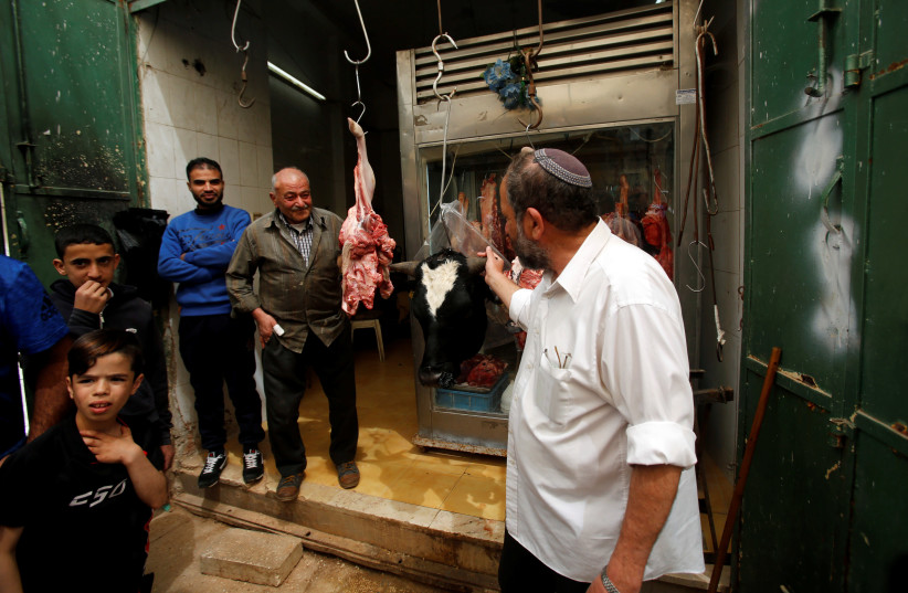 A Jewish man looks at meat at Palestinian butcher's shop in Hebron, in West Bank, 2018. (photo credit: REUTERS/MUSSA QAWASMA)