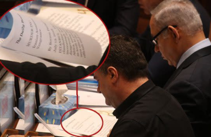 Prime Minister Benjamin Netanyahu reads in the Knesset plenum, July 17th, 2018 (photo credit: LADAAT WEBSITE)