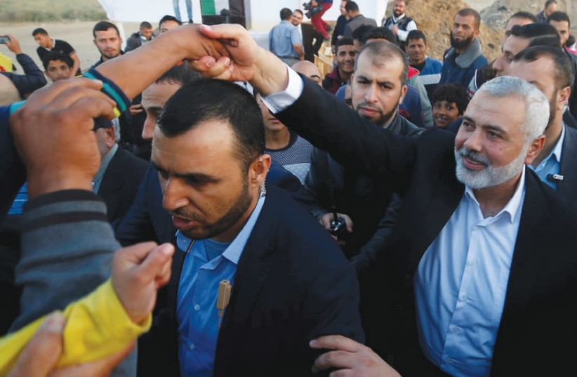 HAMAS CHIEF Ismail Haniyeh shakes hands with a boy during a protest at the Gaza border on April 9, 2018 (photo credit: REUTERS)