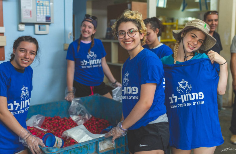 Delegation participants from the Detroit-based Sue & Alan Jay Kaufman Family Teen Mission to Israel help pack boxes of food at the Pitchon Lev aid center on Tuesday, July 10 (photo credit: ZIV TOLEDANO)