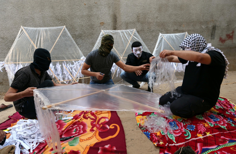 Palestinians prepare kites loaded with flammable material to be thrown at the Israeli side, near the Israel-Gaza border in the central Gaza Strip in June.. (photo credit: IBRAHEEM ABU MUSTAFA / REUTERS)