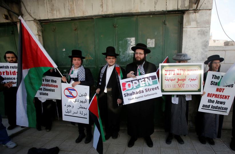 Members of Neturei Karta, a fringe ultra-Orthodox movement within the anti-Zionist bloc, attend a protest in solidarity with Palestinians in Hebron in February. (photo credit: MUSSA QAWASMA / REUTERS)