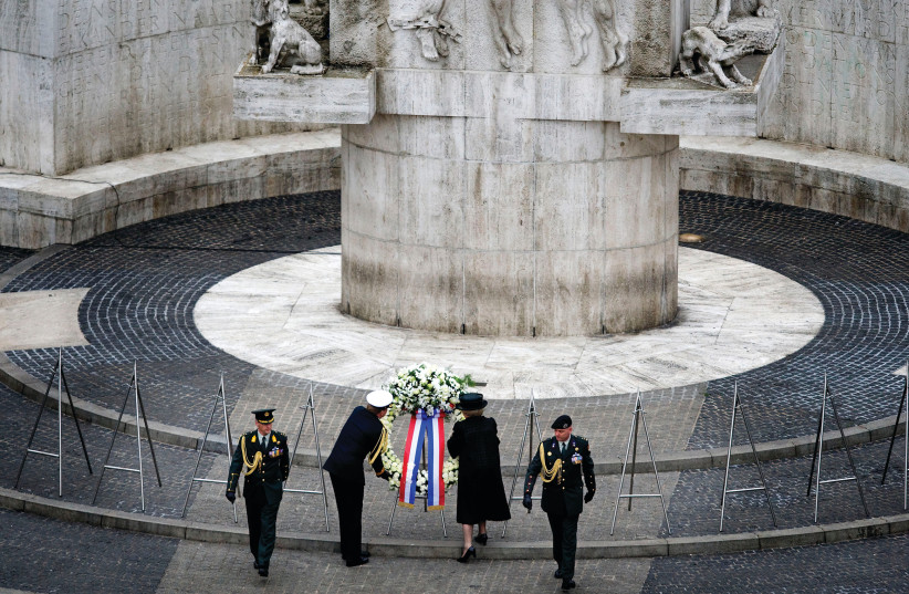 Dutch Queen Beatrix and Prince Willem-Alexander lay a garland to commemorate those who lost their lives during World War II, at the National Monument at Dam Square in Amsterdam (photo credit: REUTERS)