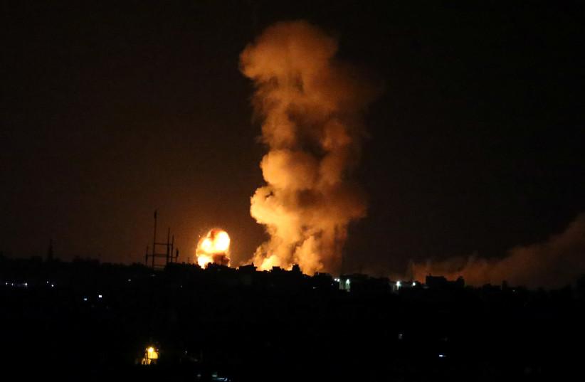 An explosion is seen following an Israeli air strike in the southern Gaza Strip July 20, 2018 (photo credit: IBRAHEEM ABU MUSTAFA / REUTERS)