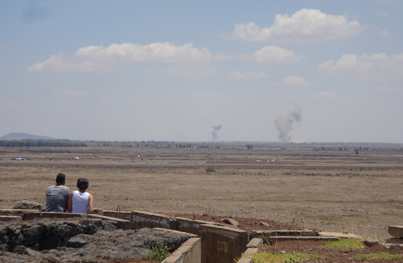 A couple watches the fighting in Syria from Tel Saqi. The Syrian regime and its Russian backers launched numerous artillery and air strikes on ISIS positions 2018 (photo credit: SETH J. FRANTZMAN)
