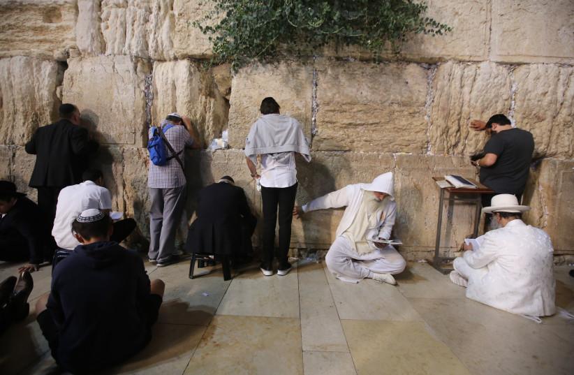 Men pray at the Western Wall, Tisha B'av, 2018 (photo credit: MARC ISRAEL SELLEM)