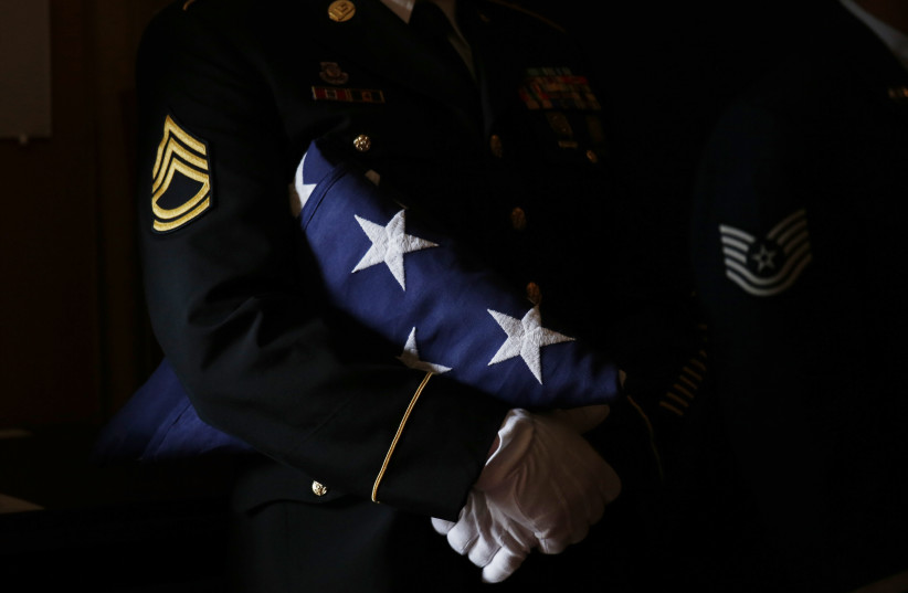A member of a US military color guard holds a folded American flag during a military funeral (photo credit: KEVIN LAMARQUE/REUTERS)