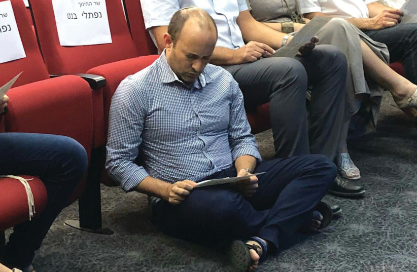 Education and Diaspora Affairs Minister Naftali Bennett sits on the floor to read the Book of Lamentations at an event commemorating Tisha Be'av in Shoham on Saturday night. (photo credit: Courtesy)