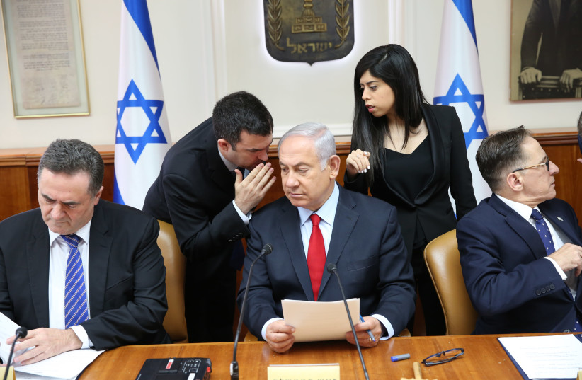 Prime Minister Benjamin Netanyahu whispering in a cabinet meeting on July 23, 2018 (photo credit: ALEX KOLOMOISKY / POOL)