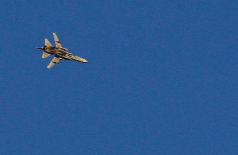 A war jet flies above Syria near the Israeli Syrian border as it is seen from the Golan Heights, Israel July 23, 2018 (photo credit: RONEN ZVULUN/REUTERS)