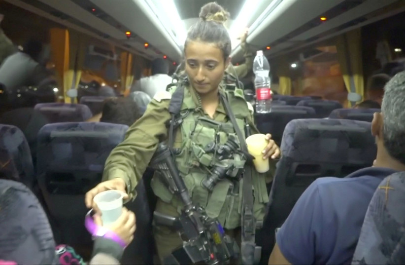 An Israeli solider hands out water on a bus, during the Syria Civil Defence, also known as the White Helmets, extraction from the Golan Heights (photo credit: IDF SPOKESPERSON UNIT VIA REUTERS)