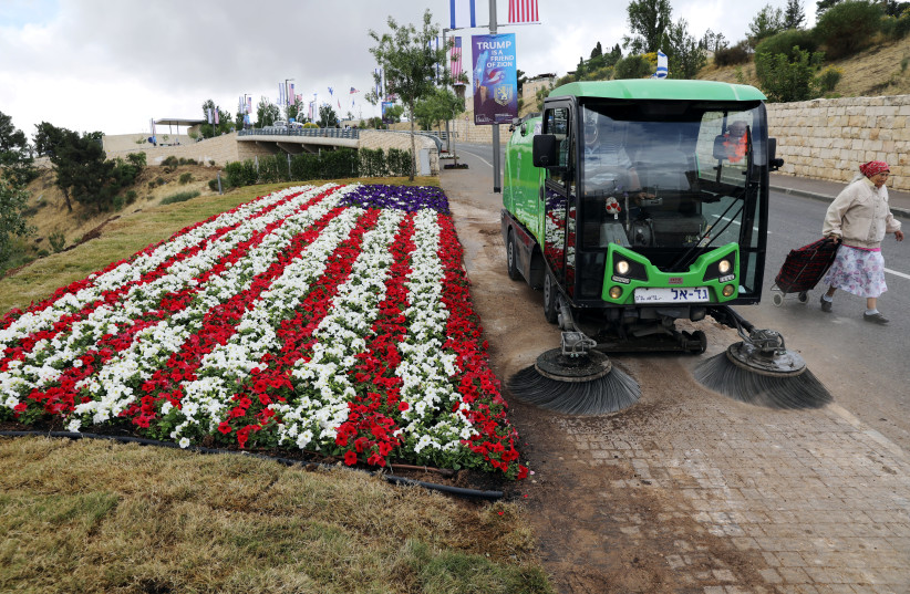 A street sweeper cleans sidewalk next to a flower bed in shape of U.S. flag, near location of new U.S. embassy in Jerusalem, 2018. (photo credit: AMMAR AWAD/REUTERS)