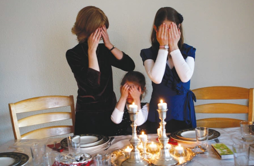 MEMBERS OF the Nogradi family light candles for Shabbat in their home in Budapest (photo credit: REUTERS)