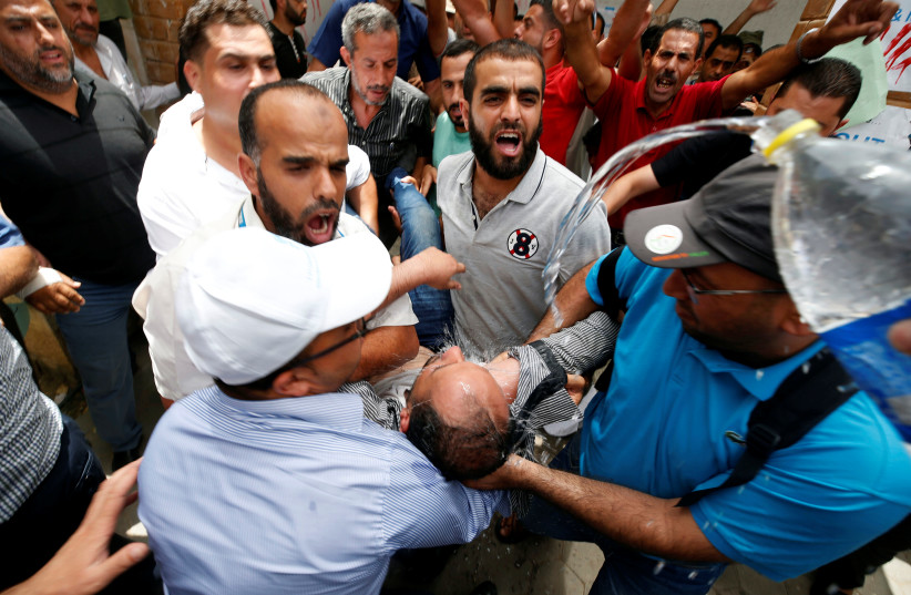 People spray water on a Palestinian UNRWA employee who tried to set himself on fire during a protest against jobs termination by UNRWA inside its headquarters in Gaza City July 25, 2018 (photo credit: MOHAMMED SALEM/ REUTERS)