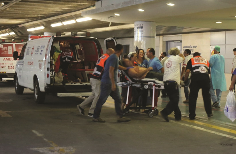 One of the victims of the stabbing attack are evacuated to Shaare Zedek Medical Center, July 26, 2018. (photo credit: MARC ISRAEL SELLEM)