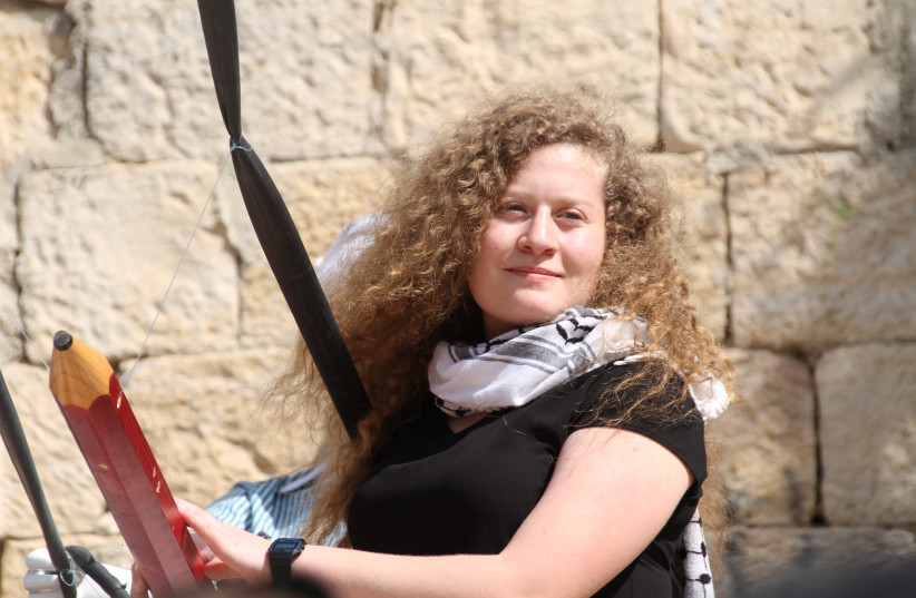 Ahed Tamimi next to a large Palestinian monument  (photo credit: TOVAH LAZAROFF)