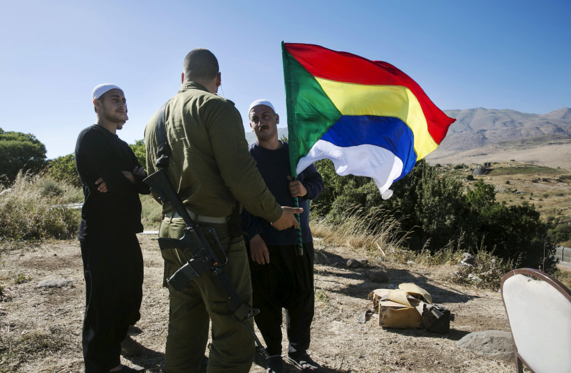 A member of the Druze community holds a Druze flag as he speaks to an Israeli soldier near the border fence between Syria and the Golan Heights, near Majdal Shams June 18, 2015. Gathered at a hilltop in the Golan Heights, a group of Druze sheikhs look through binoculars at the Syrian village of Hade (photo credit: BAZ RATNER/REUTERS)