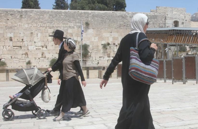 AN ARAB woman walks past a Jewish couple at the Western Wall (photo credit: MARC ISRAEL SELLEM)