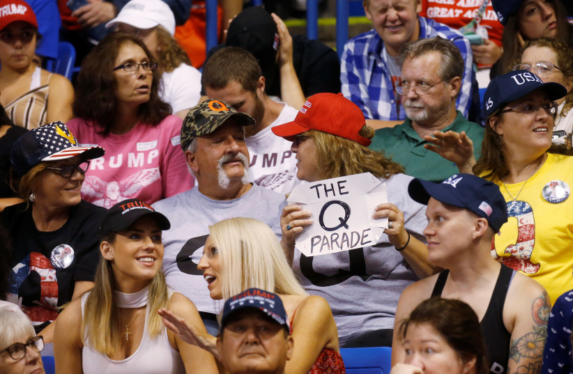 A supporter holds a QAnon sign as US President Donald Trump addresses a campaign rally at Mohegan Sun Arena in Wilkes-Barre, Pennsylvania, US, August 2, 2018 (photo credit: LEAH MILLIS/REUTERS)