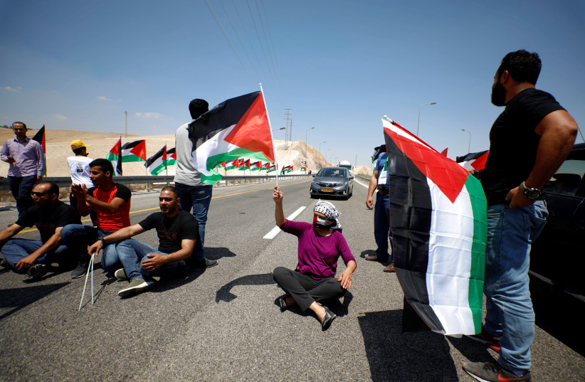 Demonstrator holds Palestinian flag during support rally of Khan al-Ahmar residents in West Bank, 2018 (photo credit: MOHAMAD TOROKMAN/REUTERS)