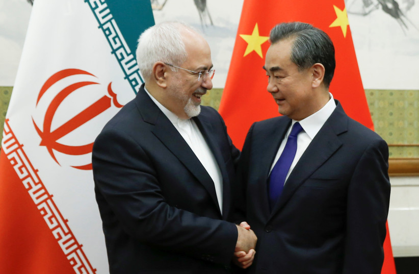 Chinese State Councillor and Foreign Minister Wang Yi meets Iranian Foreign Minister Mohammad Javad Zarif at Diaoyutai state guesthouse in Beijing, China May 13, 2018 (photo credit: THOMAS PETER/REUTERS)