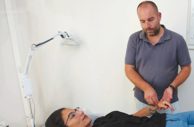 Oz Levy treats a patient (photo credit: MARC ISRAEL SELLEM)