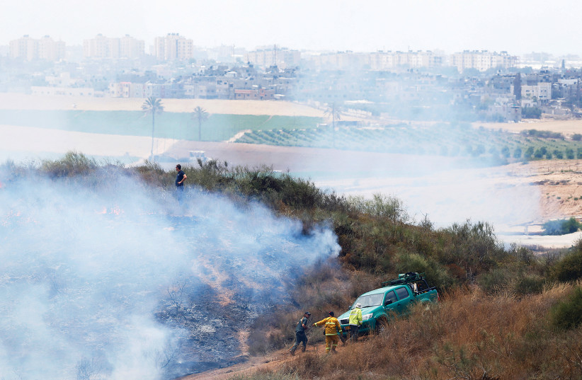 People are seen near Kibbutz Nir Am during a fire in an area where Palestinians in Gaza have been causing blazes by flying kites and balloons loaded with flammable materials.  (photo credit: AMIR COHEN/REUTERS)