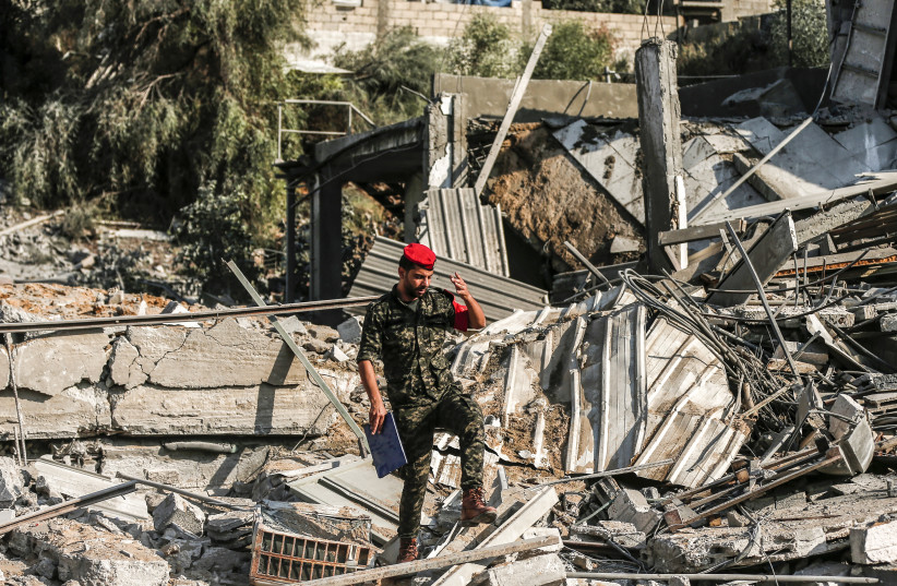 A member of Hamas' military police walks through rubble at a site that was hit by Israeli air strikes in Gaza City on August 9, 2018 (photo credit: MAHMUD HAMS / AFP)