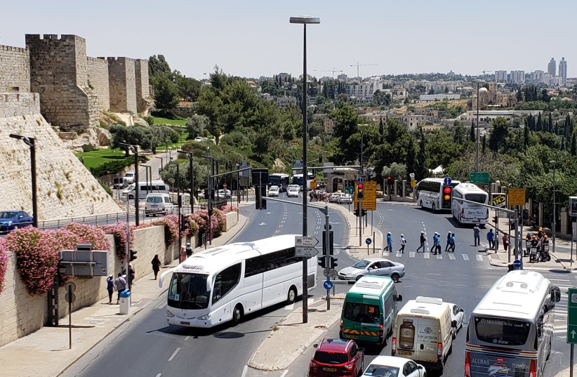 A view of Jerusalem's Old City walls near Jaffa Gate, with a tour bus in the center, August 9 2018 (photo credit: OREN OPPENHEIM)