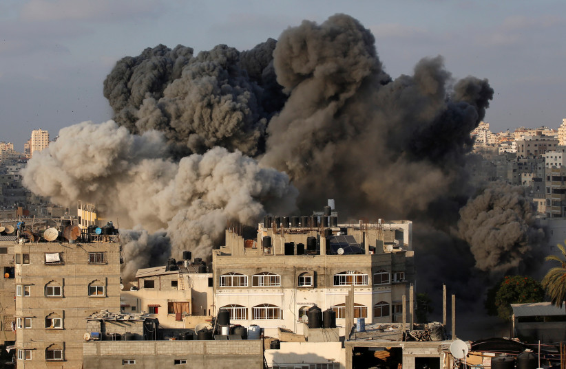 Smoke rises after an Israeli aircraft bombed a multi-story building in Gaza City August 9, 2018 (photo credit: REUTERS/MOHAMMED SALEM)