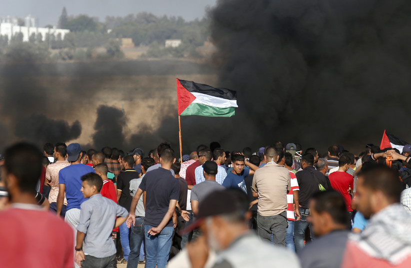 Palestinian protesters wave their national flag as they gather during a demonstration at the Israel-Gaza border, in Khan Yunis in the southern Gaza Strip on August 10, 2018 (photo credit: SAID KHATIB / AFP)
