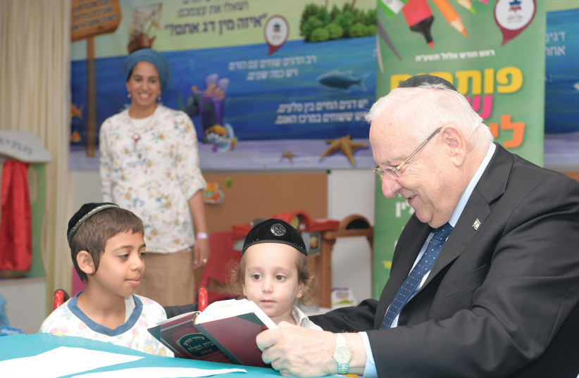 PRESIDENT REUVEN RIVLIN reads with young students taking classes at Mayanei Hayeshua Medical Center in Bnei Brak (photo credit: AMOS BEN GERSHOM, GPO)