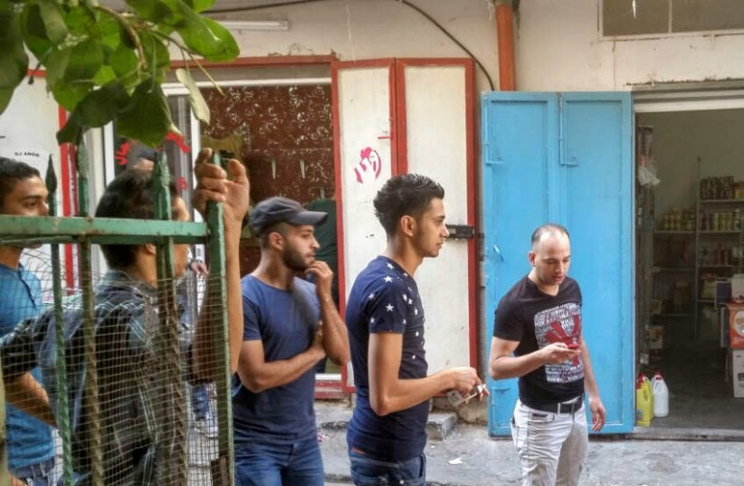 Za'bour in a black T-shirt holds his cell phone next to a group of young men from Balata refugee camp (photo credit: KHALED ABU-TOAMEH)