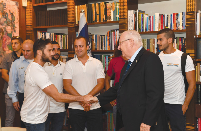 PRESIDENT REUVEN Rivlin meets with comrades in arms of the two soldiers whose bodies are still being held by Hamas.  (photo credit: KOBI GIDEON/GPO)