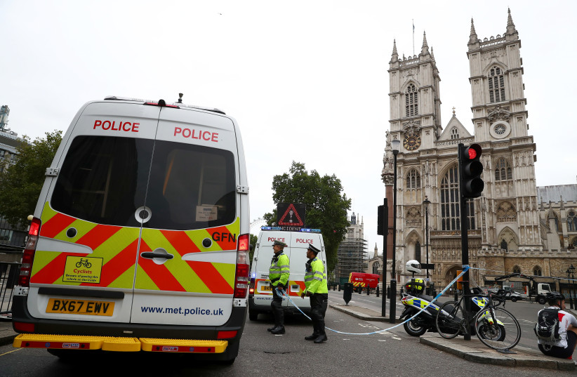 Police officers stand at a cordon after a car crashed outside the Houses of Parliament in Westminster, London, Britain, August 14, 2018 (photo credit: HANNAH MCKAY/ REUTERS)