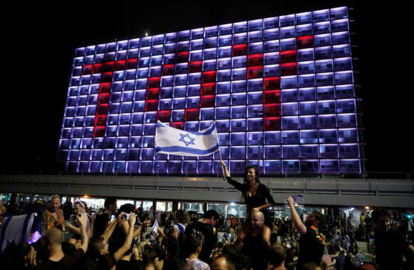 """People celebrate the winning of the Eurovision Song Contest 2018 by Israel's Netta Barzilai with her song """"Toy"""" , at Rabin square in Tel Aviv, Israel, May 13, 2018 (photo credit: REUTERS/CORINNA KERN)"""