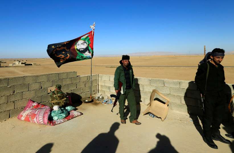 Members of a Shia militia guard a house in Iraq. The new NDAA warned about the presence of Iranian-backed militias (photo credit: REUTERS)