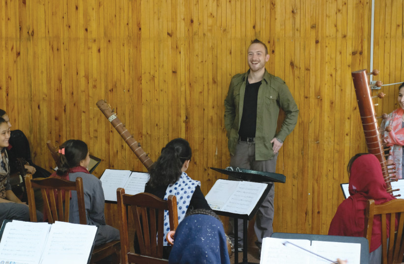 DAN BLACKWELL with members of the Zohra orchestra in Afghanistan. 'I'm coming to [Israel] from a humanitarian angle with a simple concept – promoting peace and unity and good music. (photo credit: Courtesy)