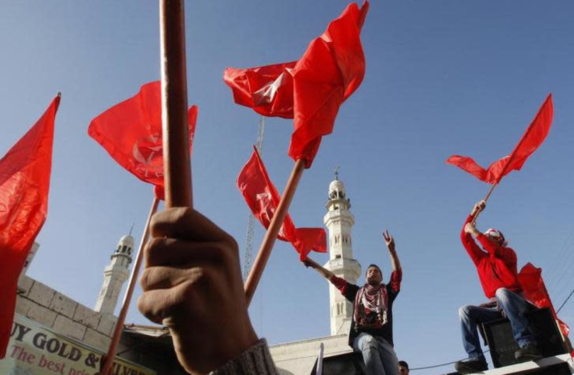 Palestinians take part in a rally organized by the Popular Front for the Liberation of Palestine (PFLP) to celebrate the 43rd anniversary of its founding in the West Bank city of Ramallah December 18, 2010 (photo credit: REUTERS/MOHAMAD TOROKMAN)