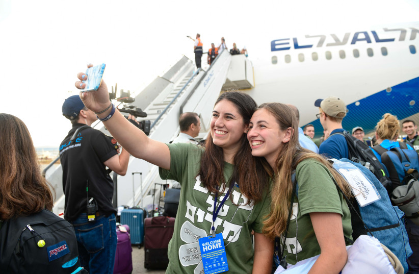 Two new Olim taking an excited selfie upon landing in Israel (photo credit: SHAHAR AZRAN)
