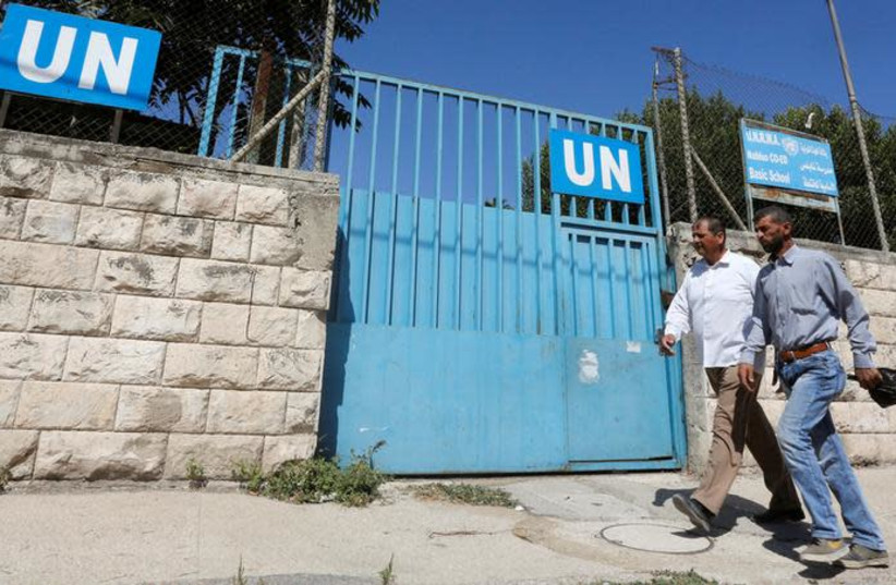 Palestinians pass by the gate of an UNRWA-run school in Nablus in the West Bank August 13, 2018 (photo credit: ABED OMAR QUSINI/REUTERS)